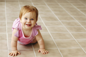 A child crawls on a floor cleaned by Hains Carpet Cleaning service.